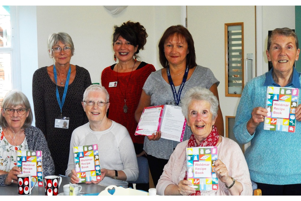 Weldmar staff, volunteers and day services patients with the recipe book